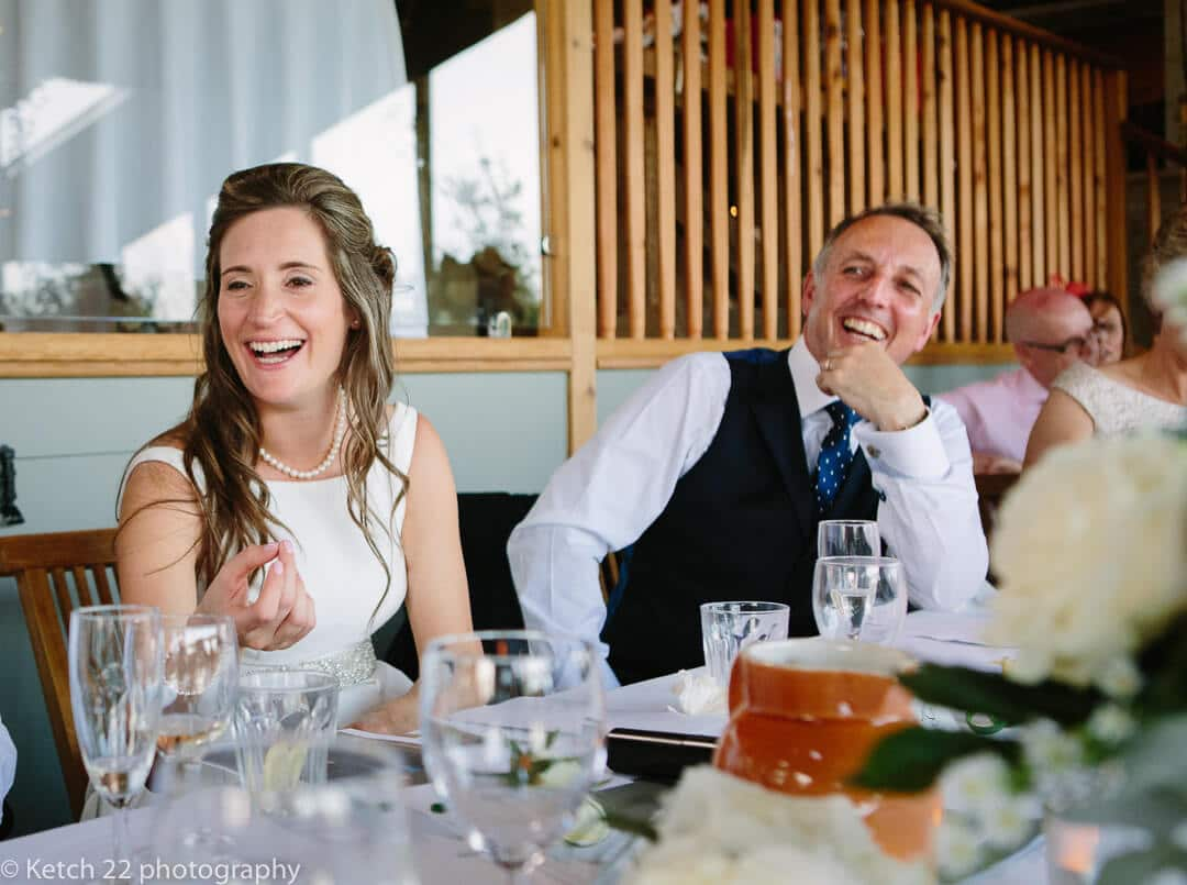 Bride and groom react during wedding speeches