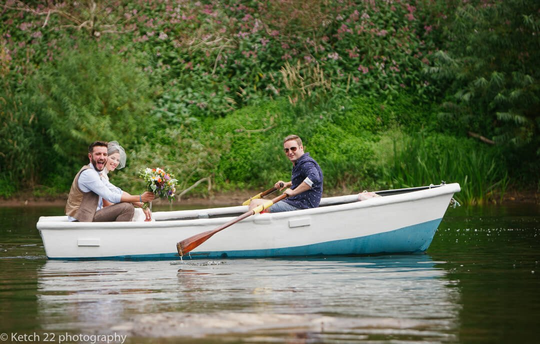 Bride and groom on rowing boat at documentary wedding