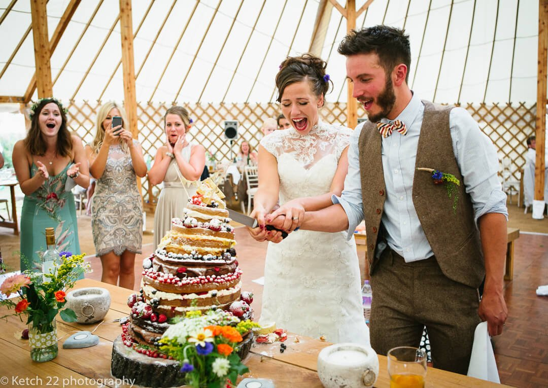 Quirky photo of bride and groom cutting wedding cake