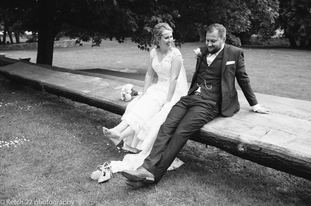 Bride with bare feet sitting on bench with groom at eastington House wedding