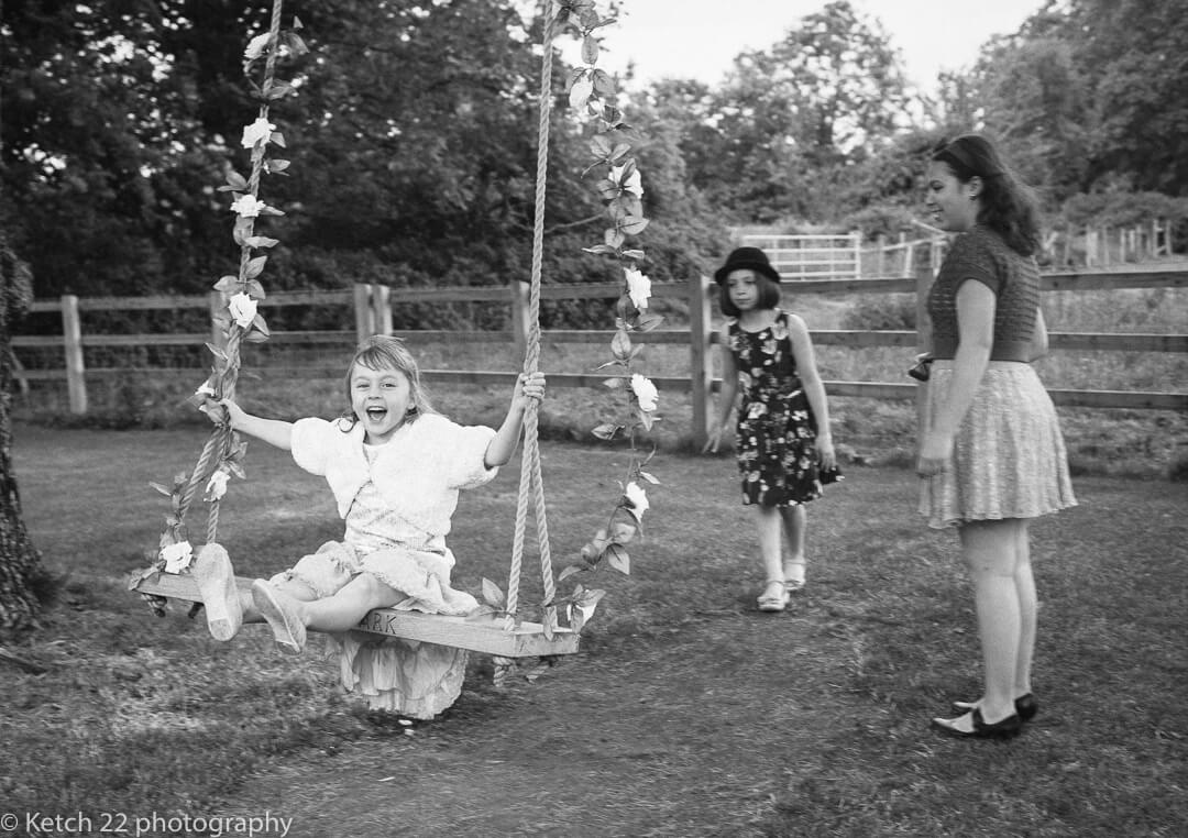 kids playing on swing at Eastington Park wedding