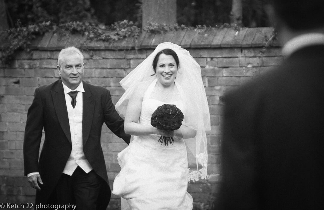 Father and bride walking towards church entrance just before Gloucester wedding ceremony