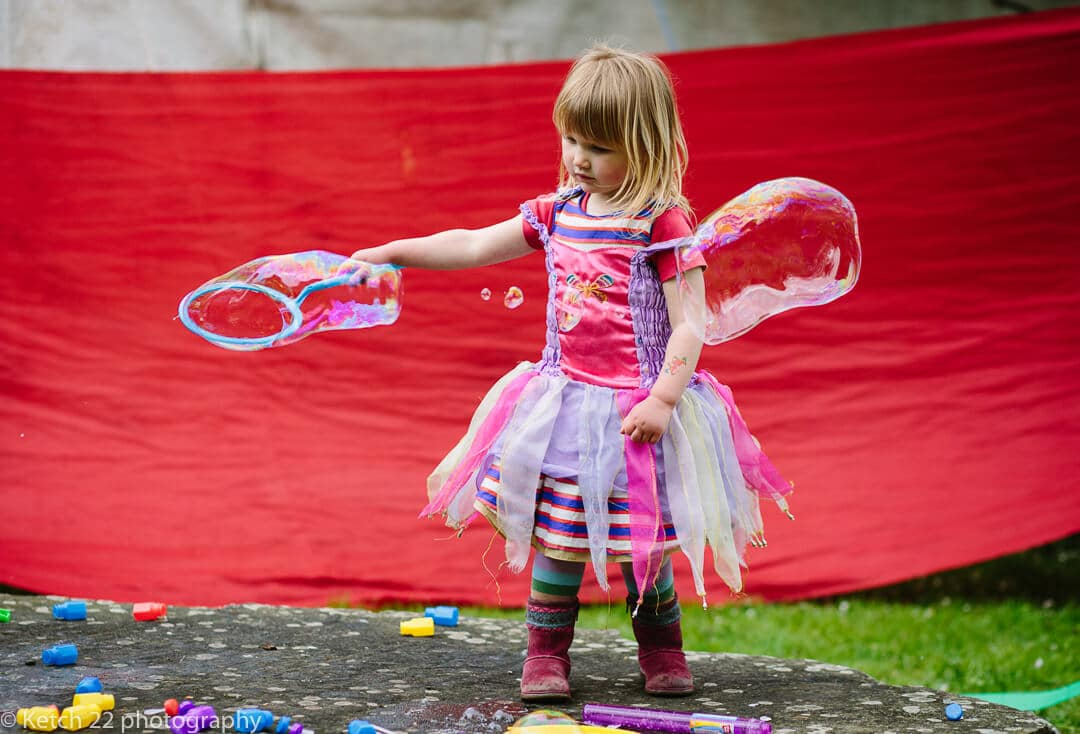 Little girl in pink dress playing with bubbles at vintage wedding