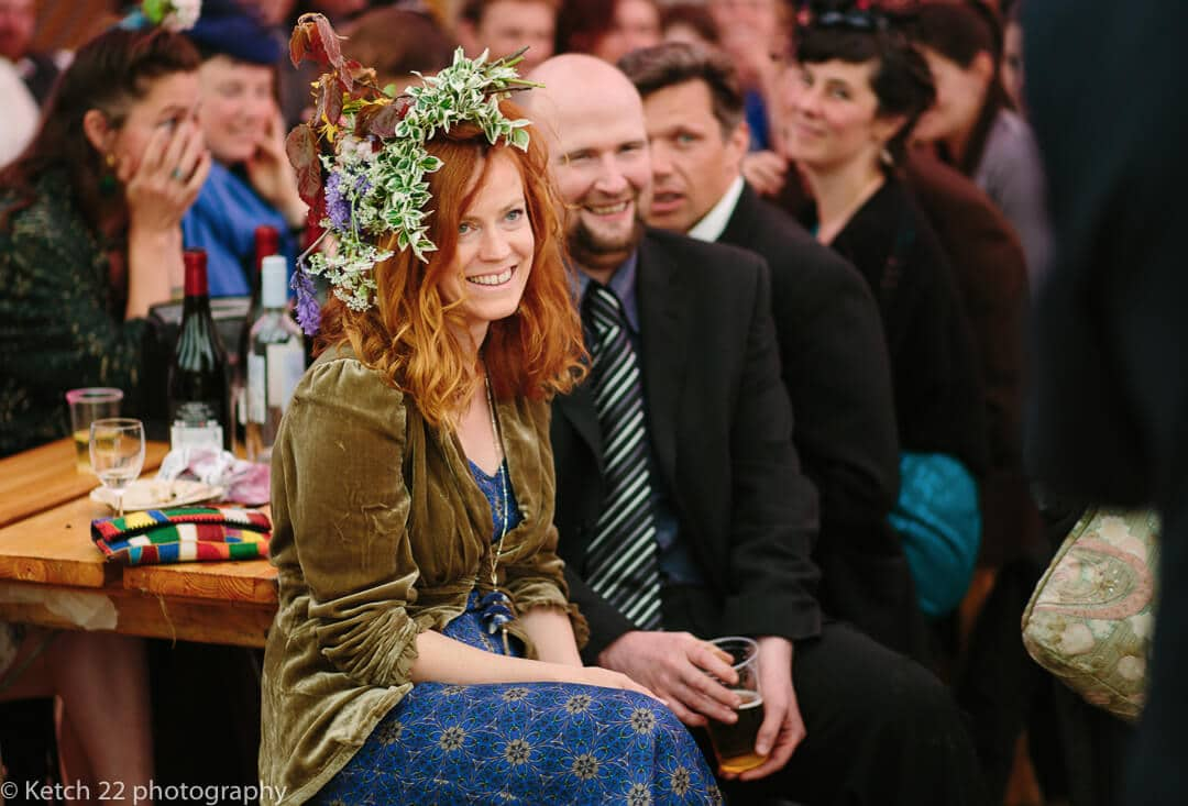 Wedding guest with flowers in her hair watching speechs