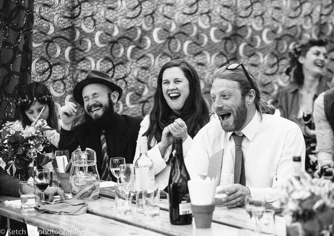 Wedding guests laughing in vintage marquee
