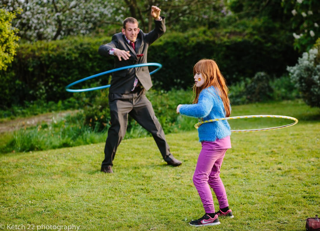Wedding guests playing with hoola hoops at summer wedding