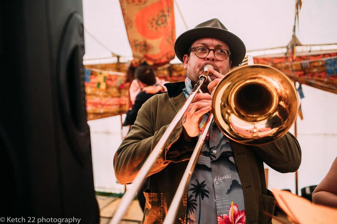 Man playing big trombone at rural wedding
