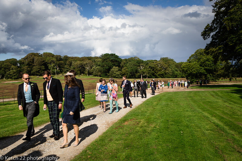 Wedding guests walking at Lulworth Castle estate in Dorset