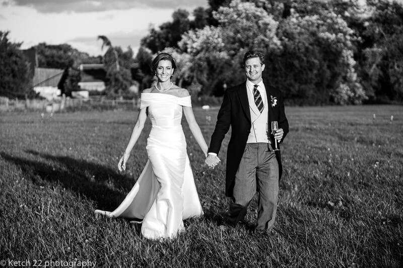 Bride and groom walking through grass field at Dorset summer wedding