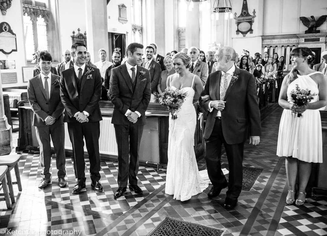Groom watches bride and father walking down church aisle