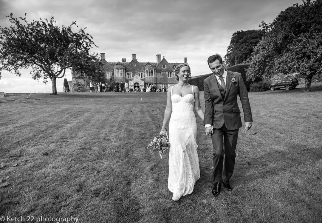 Natural photo of bride and groom walking and laughing in garden
