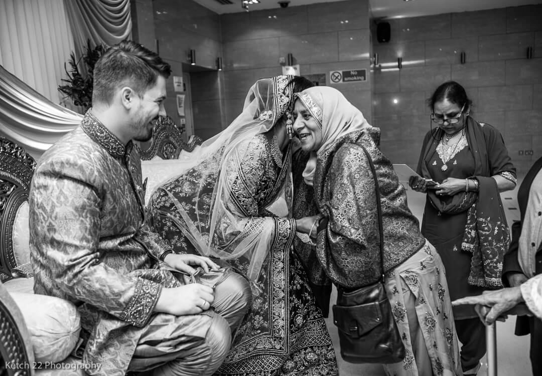 Wedding guest hugging bride at muslim wedding