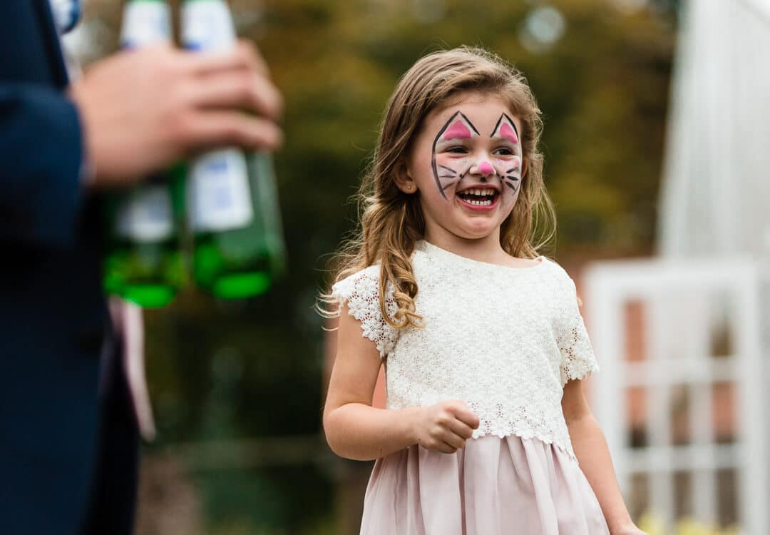 Flower girl with painted face laughing at How Caple Court