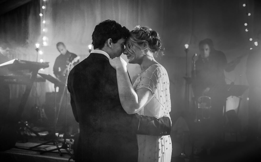 Moody black and white photo of bride and groom at first dance