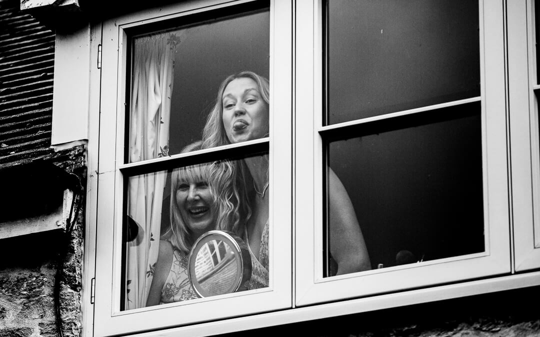 Bride and daughter looking through window and sticking out tongues