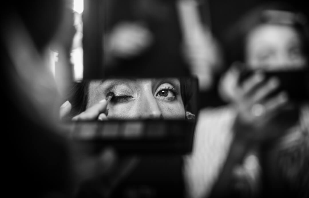 Bride applying make up whilst looking in mirror at preparations