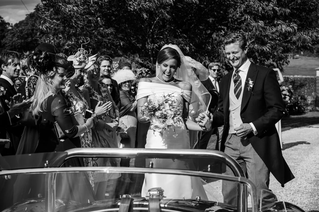 Bride and groom stood up in wedding car getting showered with confetti