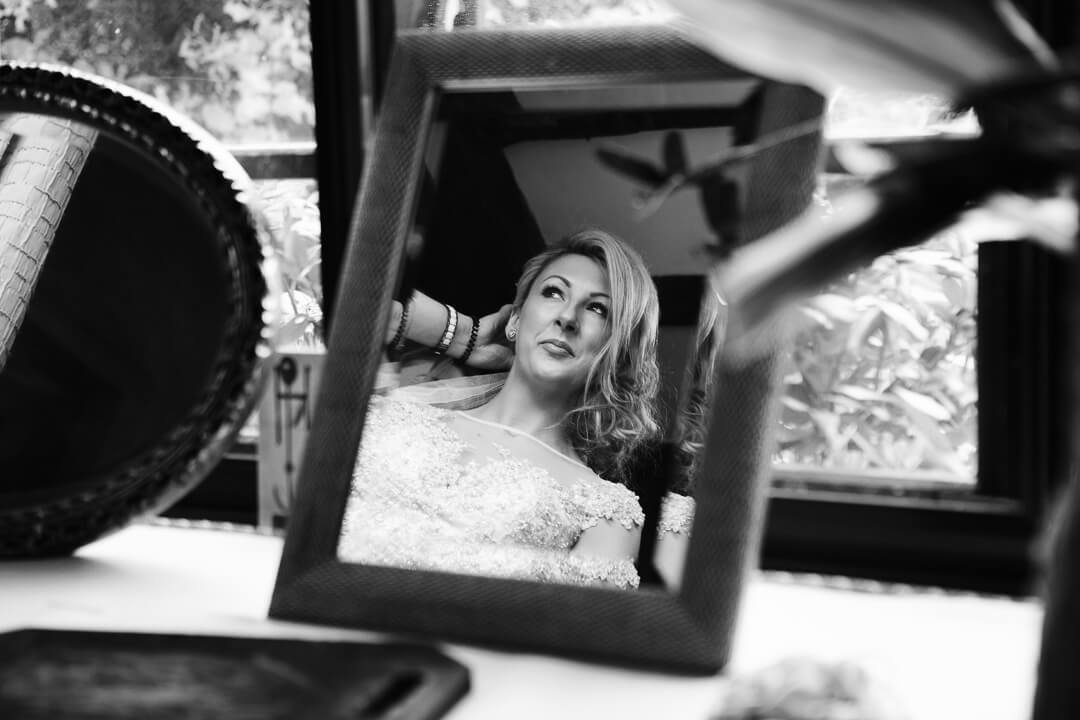 Bride with blonde hair looking in mirror during preparations