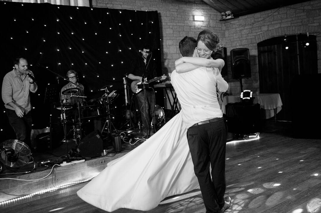 Groom swinging laughing bride at barn wedding