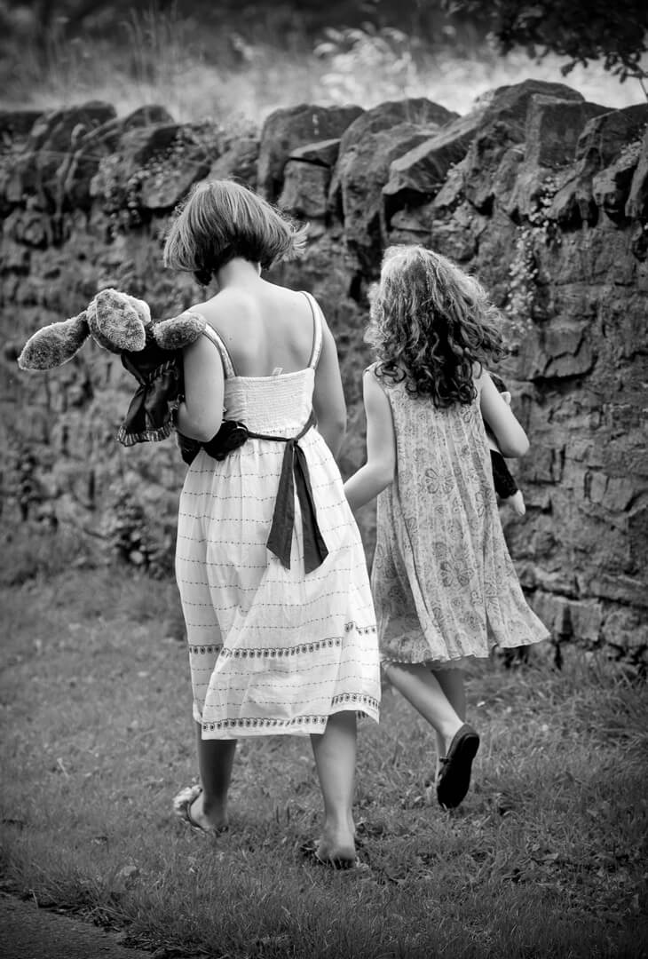 Two young sisters carrying teddy bear walking down lane