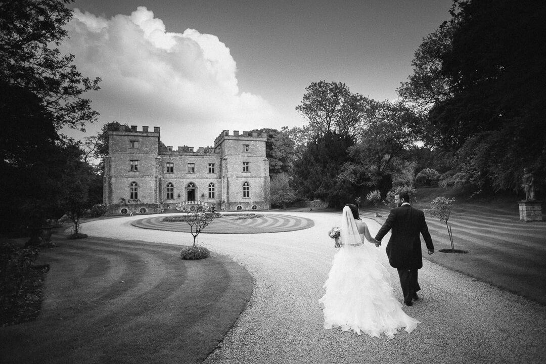 Bride and groom walking hand in hand at Clearwell Castle wedding