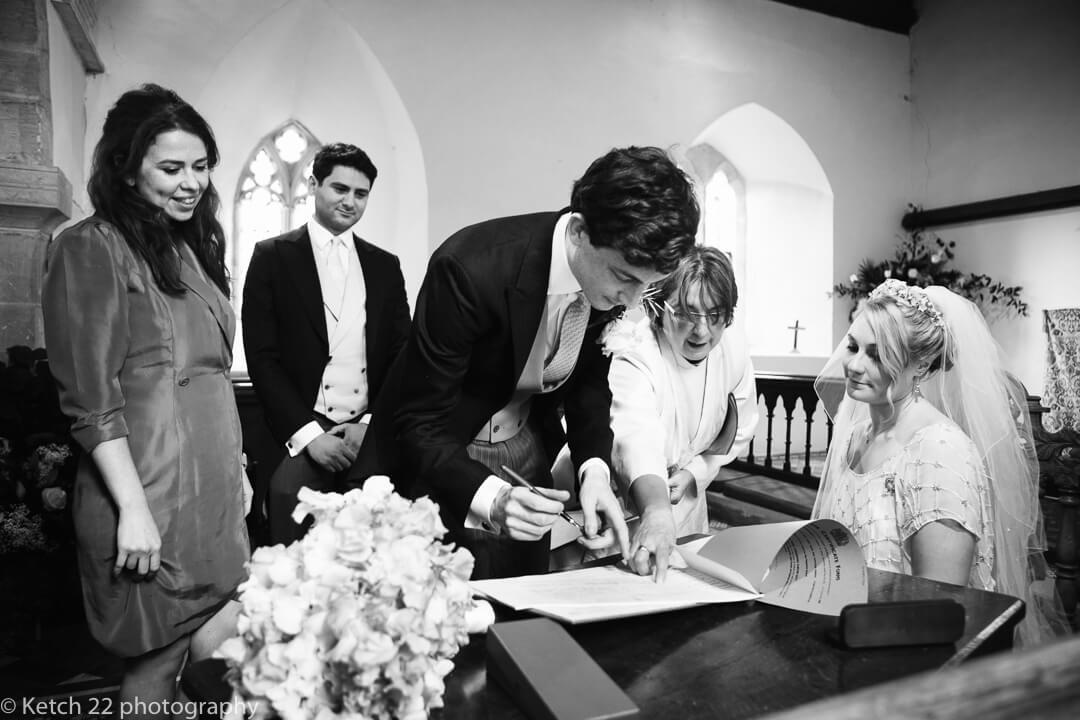 Groom signing registrar at wedding ceremony in Church