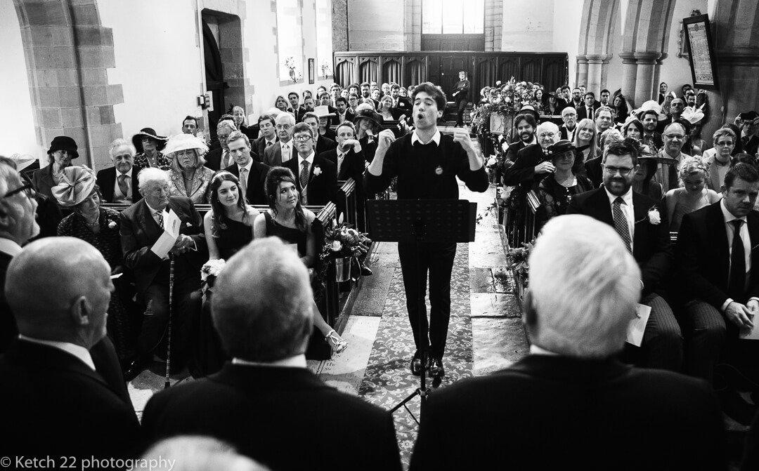 Conductor and choir singing at Church wedding