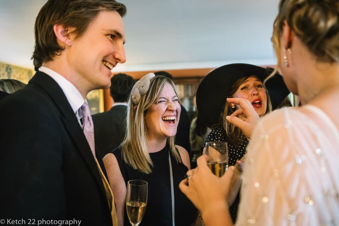 Wedding guests laughing and chatting at reception