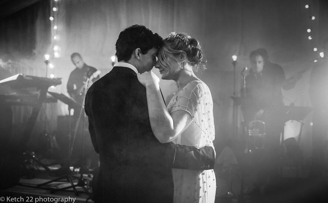 Moody black and white photo of bride and groom having their first dance