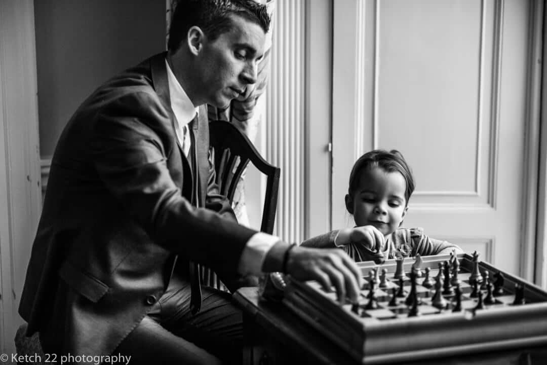 Father and daughter playing chess at photojournalistic wedding