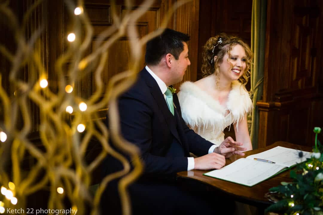 Bride and groom signing the registrar after Winter wedding ceremony