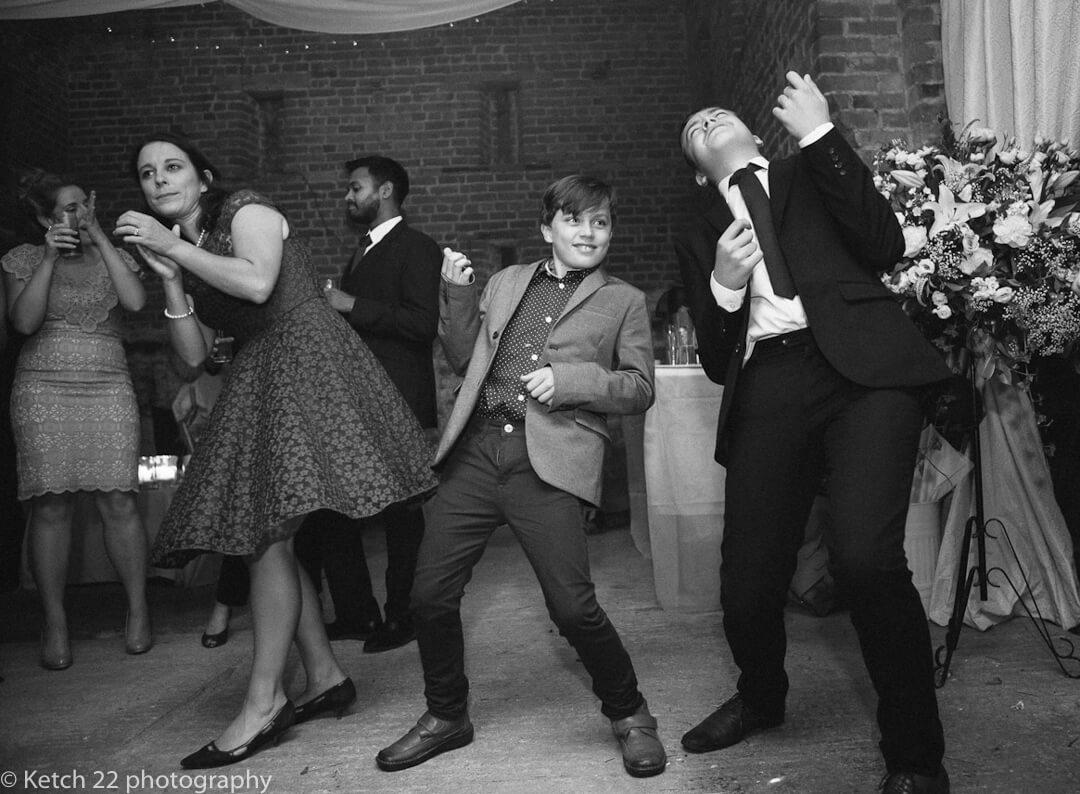 Teenage kids playing air guitar at wedding reception