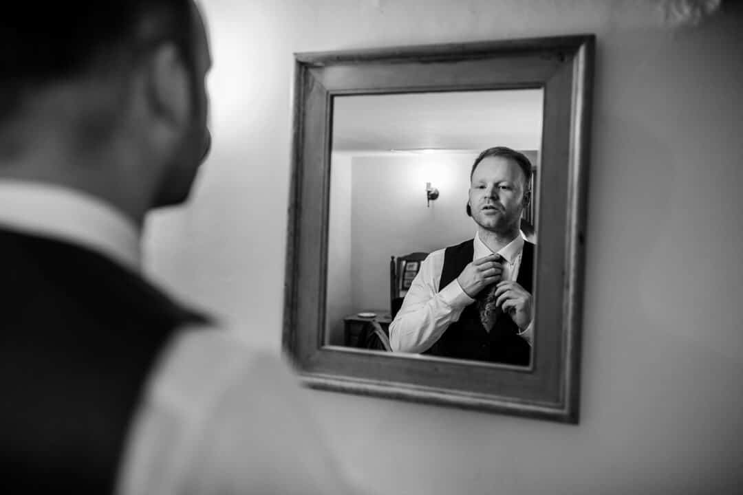 Groom putting on tie in mirror at wedding