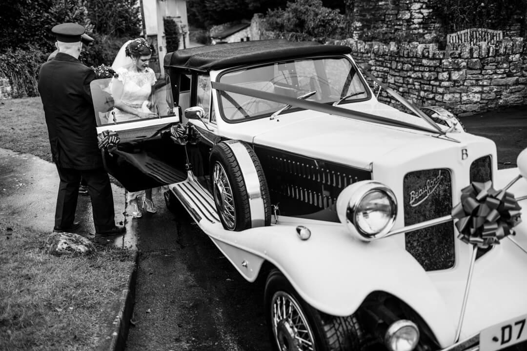 Bride getting into wedding car