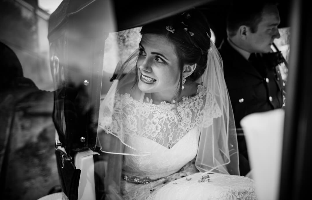 Documentary wedding photo of bride looking out of wedding car