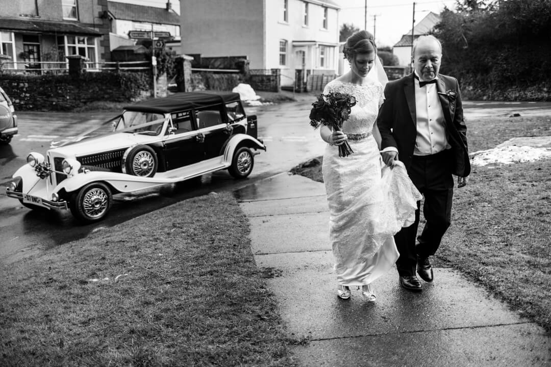 Bride and father leaving wedding car