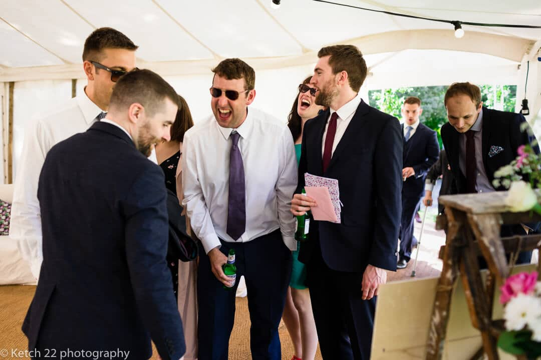 Wedding guests looking at seating plan and laughing