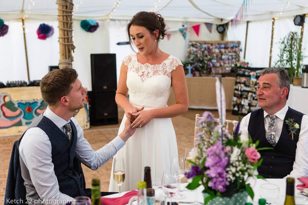 Bride holding grooms hand as she makes a speech
