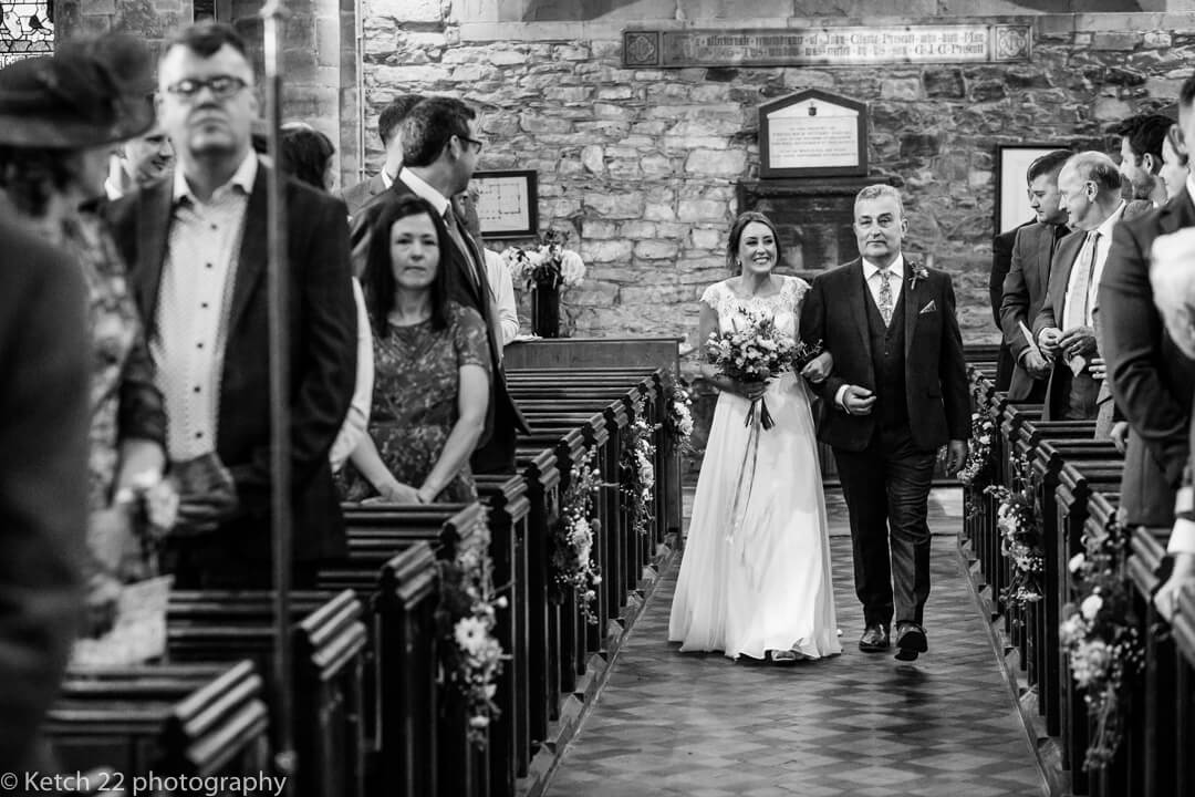 Bride and father entering the church at rural wedding
