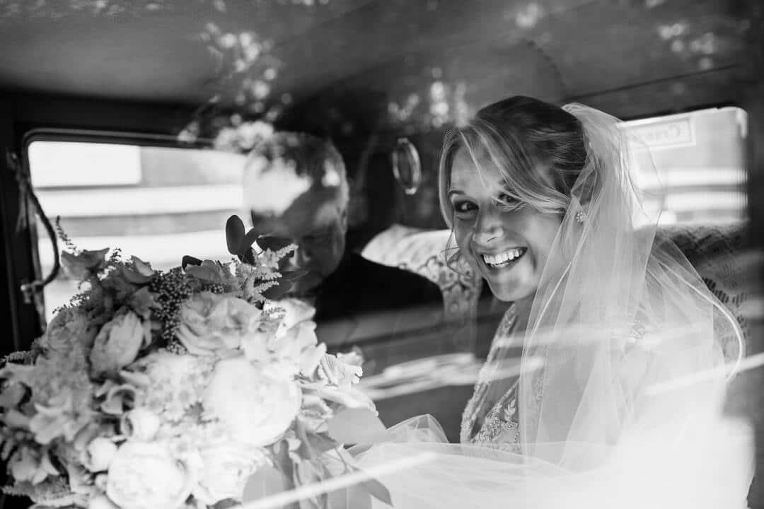 Bride smiling through wedding car window