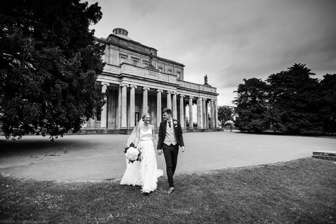 Bride and groom walking in front of Cheltenham pump rooms