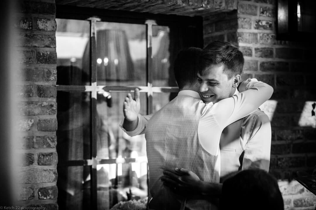 Groom hugging best man at speeches