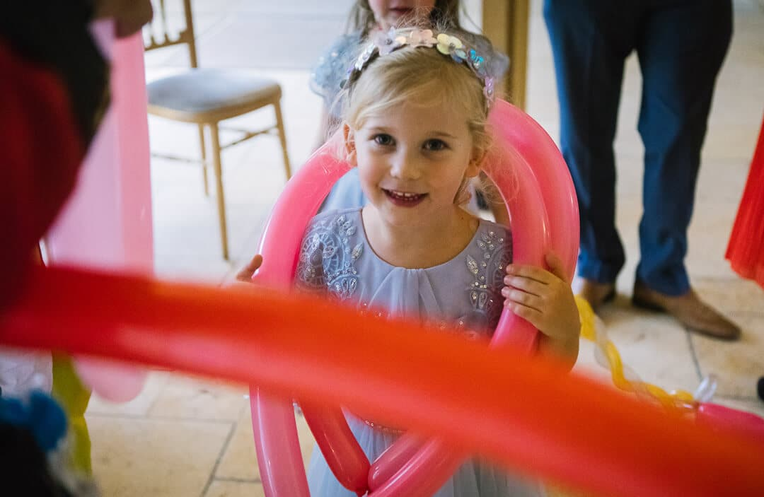 Flower girl with red balloons at wedding