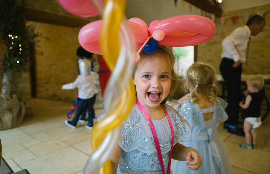 Flower girl playing with balloons at Kingscote barn Wedding