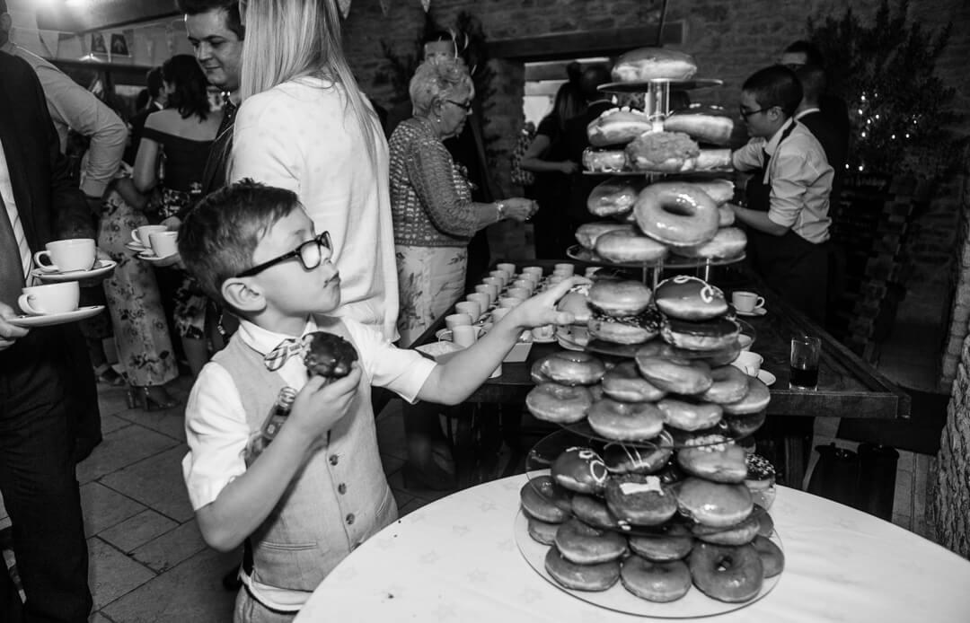 Page boy eating donuts at barn wedding