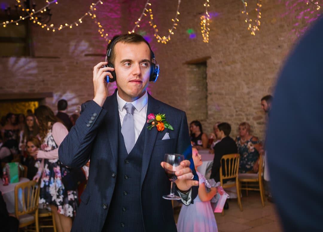 Groom listening to music on head phones at wedding