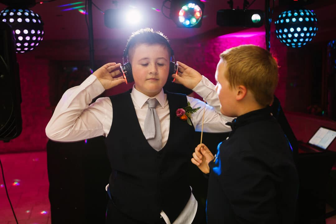 Page boy listening to wedding music on head phones