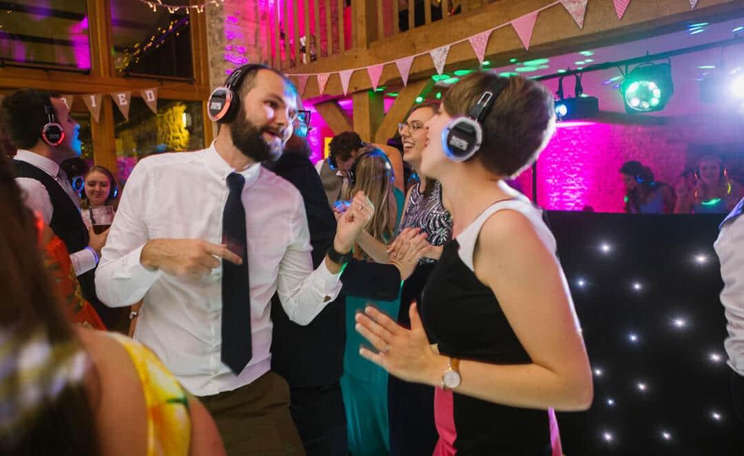 Wedding guests dancing at at silent party at barn wedding