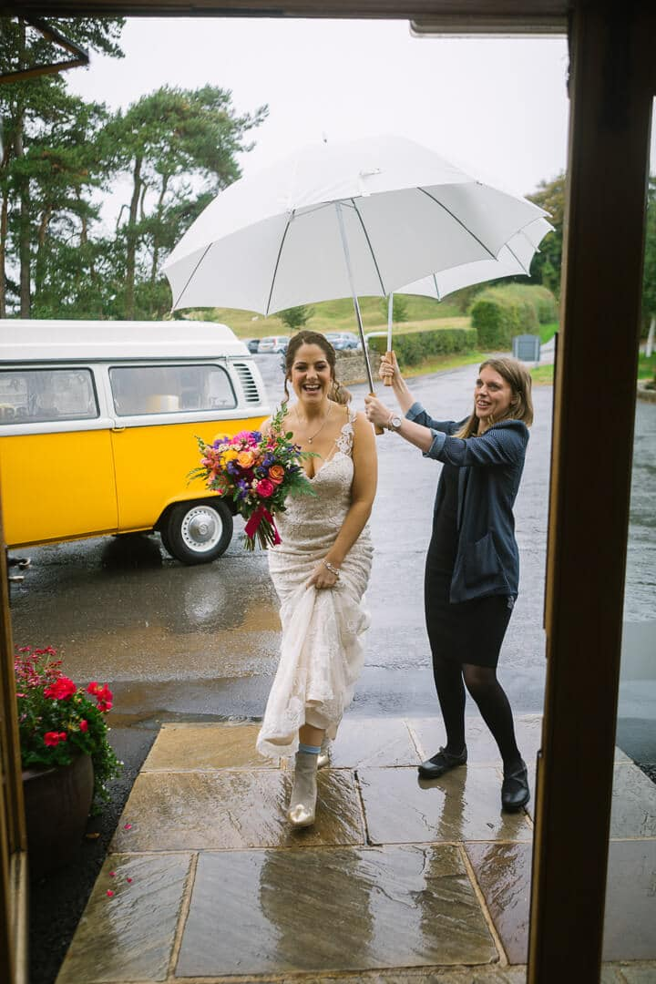 Bride arrives at Kingscote Barn wedding in the rain