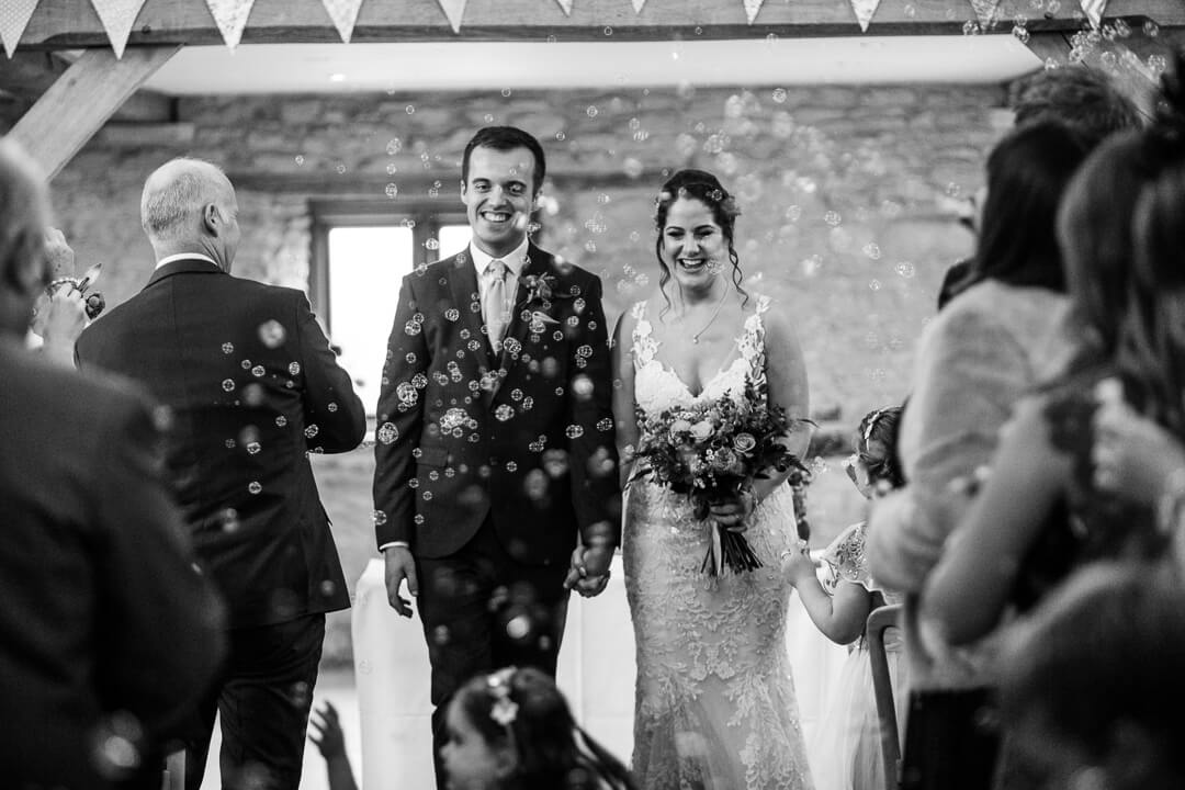 Bride and groom getting covered in bubbles at Kingscote Barn Wedding